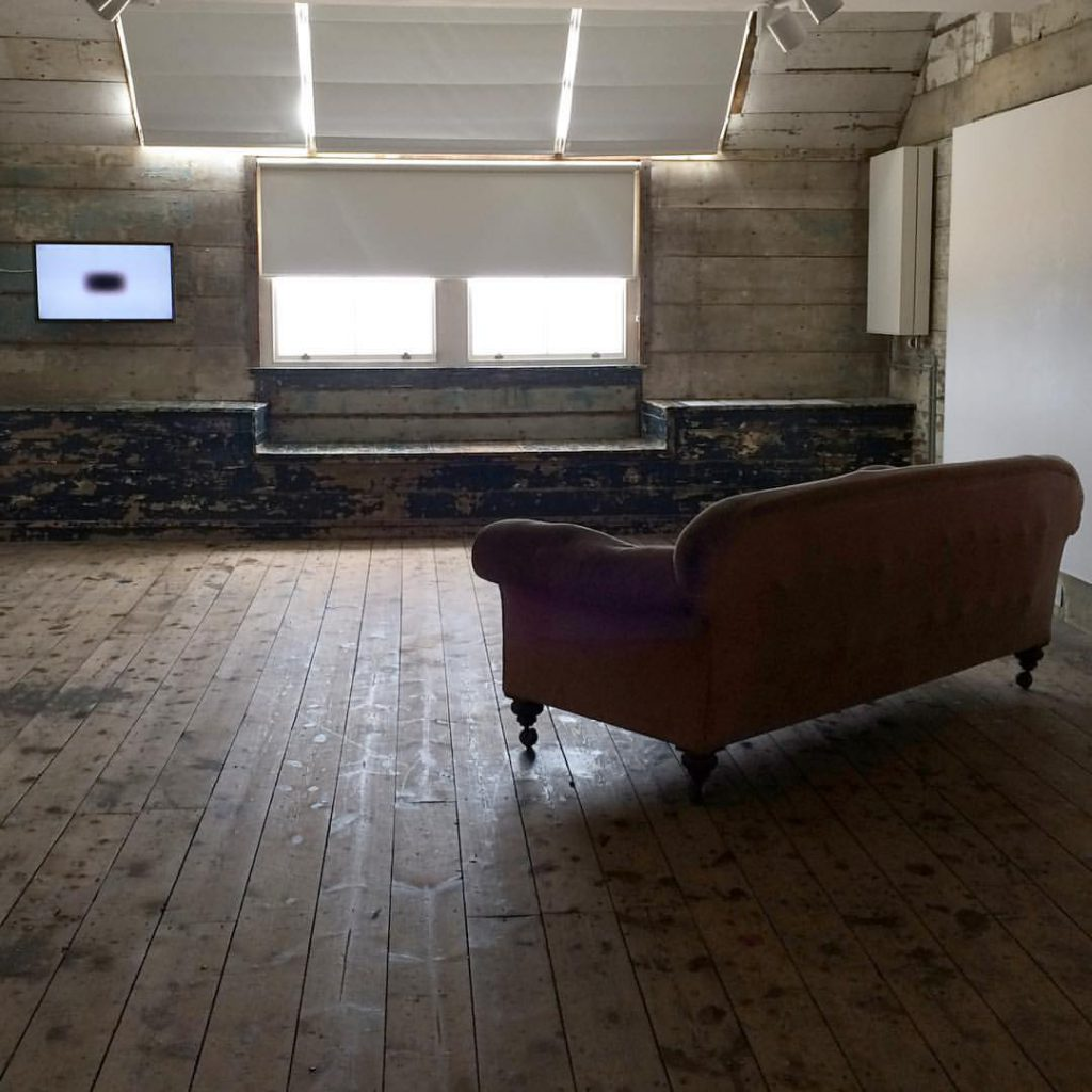 Photograph of room with wooden floor with sofa in middle and tv screen with white background image and small black square at end of room