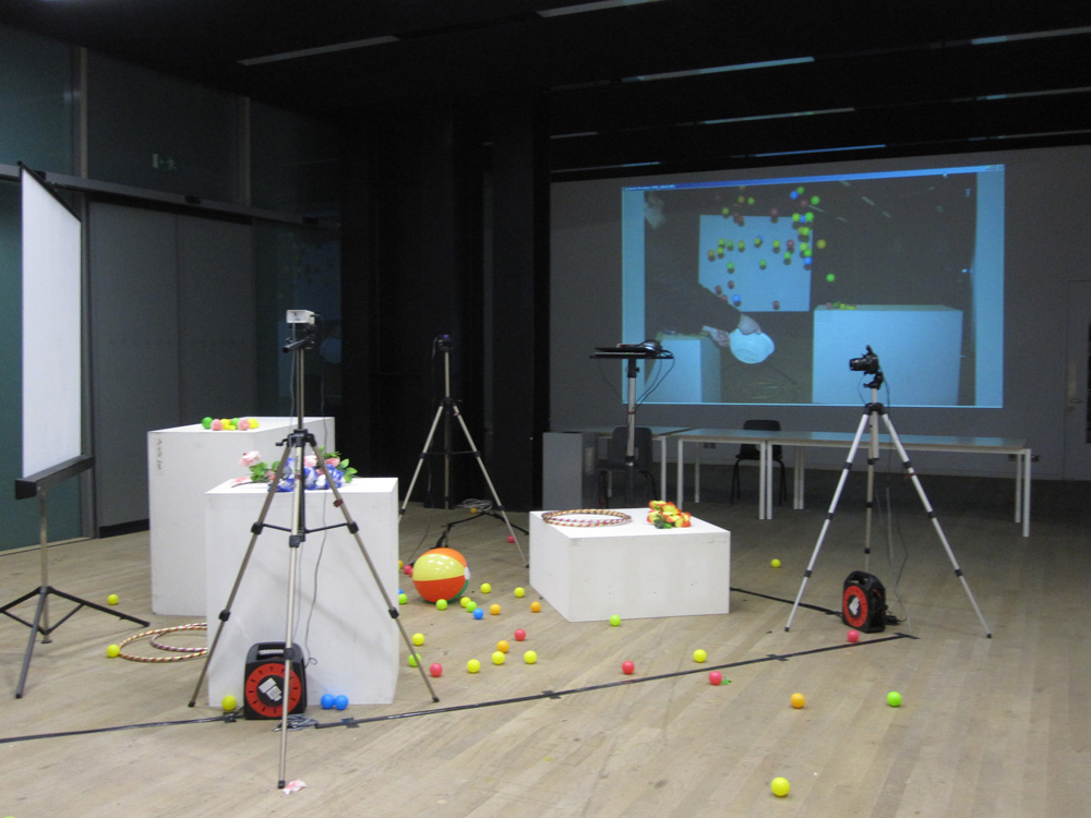 Camera and white plinths and balls in studio
