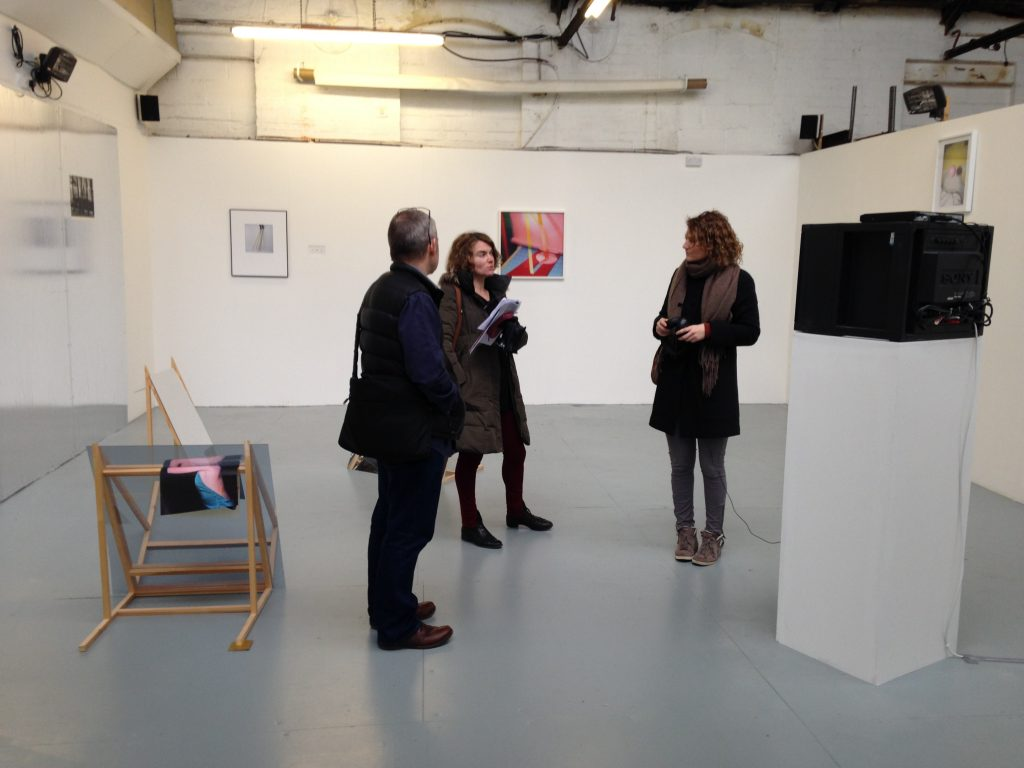Three people in a gallery with floor based works - photographs lying on wooden A frame sculptures, colour photographs on the wall and a head height monitor.